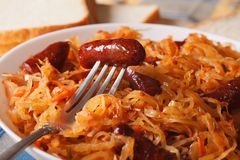 Sauerkraut with sausage macro in a white plate. Horizontal Stock Photos