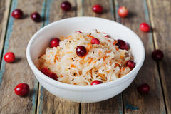 Sauerkraut or sour cabbage with cranberries in a white bowl on rustic wooden table Stock Photo