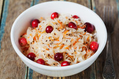 Sauerkraut or sour cabbage with cranberries in a white bowl on rustic wooden table Stock Photography