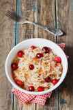 Sauerkraut or sour cabbage with cranberries in a white bowl on rustic wooden table Stock Images
