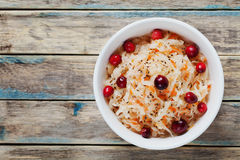 Sauerkraut or sour cabbage with cranberries in a white bowl on rustic wooden table Royalty Free Stock Photography