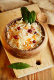 Sauerkraut - Sour cabbage -  on wooden bowl with bay leaves Stock Photo