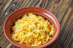 Sauerkraut on wooden background. Fermented cabbage - Sauerkraut with herbs and spices on the wooden background. Cabbage stew in ceramic bowl Stock Photo