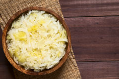 Sauerkraut. In wooden bowl, photographed overhead on dark wood with natural light (Selective Focus, Focus on the top of the Stock Photo
