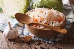 Sauerkraut in a wooden plate closeup and ingredients. Stock Photo