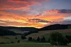 Sauerland, Duitsland - Dramatische roze en oranje zonsondergang over een groene vallei met beboste heuvels in de afstand Stock Fotografie