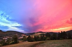 Sauerland, Germany - Rear view of a disappearing thunderstorm at sunset with dramatic blue and pink cloudscape over wooded hills royalty free stock photos