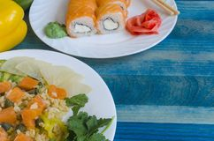 Saumoné avec du riz et des légumes du plat blanc de sushi avec des saumons sur la vue en gros plan de fond en bois bleu d'en haut image libre de droits
