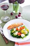 Saumons avec de la salade végétale et le vin rouge Photographie stock libre de droits