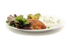 Saumons avec du riz, la salade et des légumes Images libres de droits
