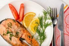 Saumons, citron et tomates rôtis du plat blanc Photos stock