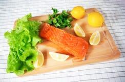 Saumons crus frais sur la planche à découper Photo stock