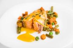 Saumons cuits au four avec les haricots verts, les carottes, les pois, le thym et la sauce orange d'un plat blanc Photographie stock libre de droits