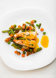 Saumons cuits au four avec les haricots verts, les carottes, les pois, le thym et la sauce orange d'un plat blanc Photos stock