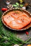 Saumons dans la casserole frite avec des ingrédients sur la table de cuisine rustique Photographie stock