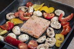 Saumons et légumes sur le gril Plan rapproché sur griller les poivrons saumonés, rouges et jaunes carrés de forme, tomates-cerise photo stock