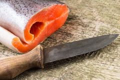 Saumons frais sur le conseil en bois avec le couteau Image stock