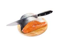 Saumons frais sur un panneau de découpage rond Photos stock