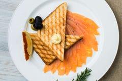 Saumons fumés avec l'aneth frais sur la tranche de pain, dans la lumière naturelle, nourriture authentique poissons salés rouges  Photo stock