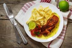 Saumons grillés avec de la sauce à safran et des pâtes de tagliatelles, cerise photos stock