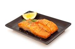 Saumons grillés avec le citron d'isolement sur le blanc Images stock
