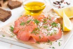 Saumons, pain et ingrédients salés sur un conseil en bois, plan rapproché Photographie stock