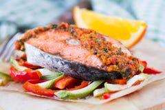 Saumons rouges de poissons de bifteck sur les légumes, la courgette et le paprika Photographie stock libre de droits