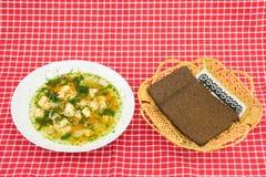 Saumons sains de soupe à poissons et pain entier de grain dans le panier sur le rouge photos stock