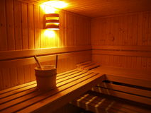Sauna 01. Sauna interior with bucket beneath a lamp Royalty Free Stock Photography