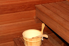 Sauna. Inside of a sauna room with water bucket in foreground Stock Image