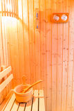 Sauna accessories in sauna room, wooden bucket place on bench an Stock Photography