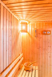 Sauna accessories in sauna room, wooden bucket place on bench an Stock Images