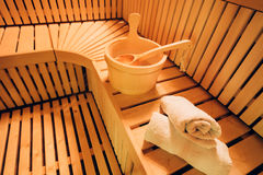 Sauna accessories. Traditional wooden sauna for relaxation with bucket of water and set of clean towels Royalty Free Stock Photo