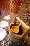Sauna bucket. A sauna interior tiled with small tiles. Wooden bucket and spoon in the foreground royalty free stock image