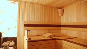 Sauna da madeira Parede de pedra com iluminação do interior Acessórios clássicos para o banho Concha e cubeta, fogão com rochas q vídeos de arquivo