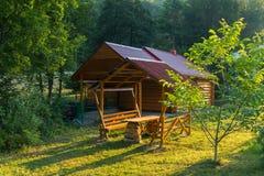 Sauna dans une maison faite de rondins et bancs en bois avec une table pour le repos se tenant sous un auvent Tout est localisé Photos libres de droits