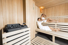 Sauna heater and girls relaxing Stock Images