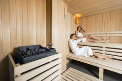 Sauna heater and girls relaxing Royalty Free Stock Photos
