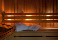 Sauna interior. Interior for a finnish sauna with white bathrobes leaving room for type stock photo