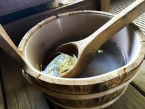 Sauna Bucket and Ladle - Reflection. Reflect and relax in sauna spa interior Finnish sauna wooden bucket with nature reflecting in water for health and healing stock image