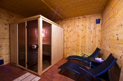Sauna interior with two sunbeds and cherry wood walls. A home sauna interior with two sunbeds, cabin and cherry color wooden walls Royalty Free Stock Image