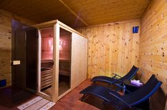 Sauna interior with two sunbeds and cherry wood walls. A home sauna interior with two sunbeds, cabin and cherry color wooden walls Royalty Free Stock Images