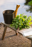 Sauna objects on wooden bench before lake at summer. Birch whisk and other sauna objects on wooden bench by lake in Finland at midsummer Royalty Free Stock Photos