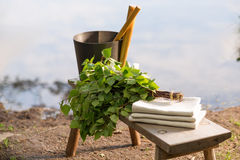 Sauna objects on wooden bench before lake at summer Royalty Free Stock Images