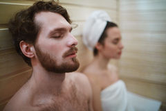 Sauna relax. Peaceful men and his wife relaxing in sauna at leisure stock image