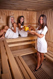 Sauna serve. Two woman relaxing in sauna and serve drinks from waiter stock photo