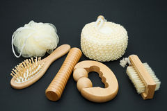 Sauna Set. Bath set - massage brush with wooden studs, massage roller, sponge, loofah, nylon tuff on a dark background Royalty Free Stock Images