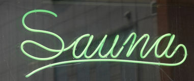 Sauna Sign. A green neon sign in a window that reads Sauna Stock Photo