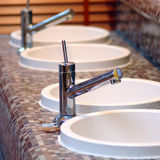 Sauna sinks. Row of round sauna sinks with chrome taps, brown tiles architecture detail stock image