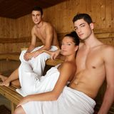 Sauna spa therapy young beautiful people group. Sauna spa therapy beautiful young people group in warm wood room white towel royalty free stock photography